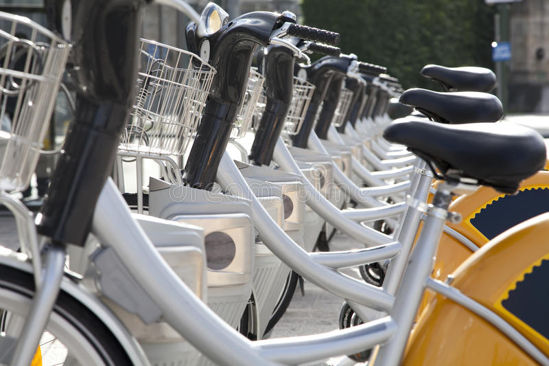 City Bikes for rent. Bicycles parked in a row on a city street royalty free stock images