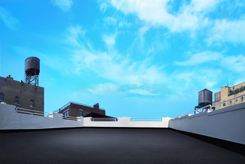 City building rooftop deck with watertowers and blue nice day sky and clouds stock image