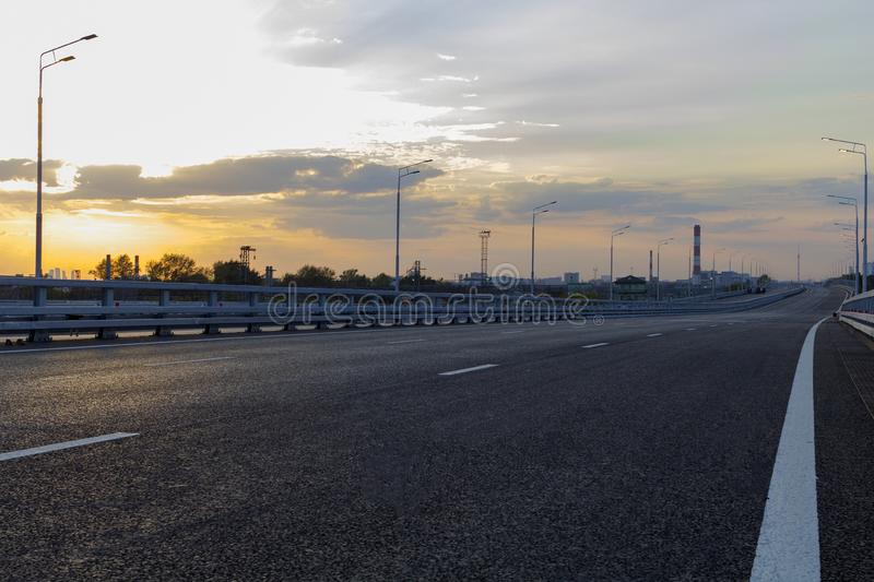 City building street scene and road surface. In evening.Sunset and clouds in the sky stock photography