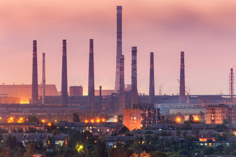 City buildings on the background of steel factory with smokestacks at night. Metallurgical plant with chimney. steelworks. Iron works. Heavy industry. Air stock images