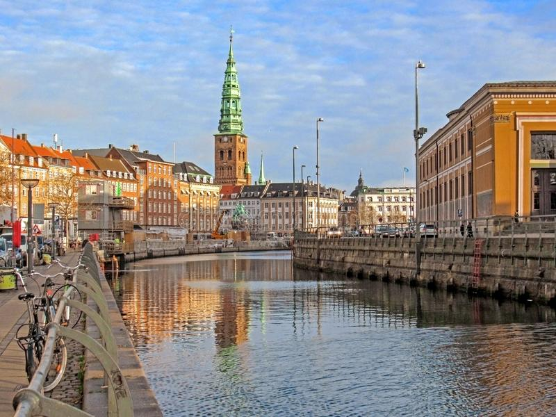 City canal and historical buildings of Copenhagen with St. Nikolaj Contemporary Art Center in Church, conspicuous landmark of stock images