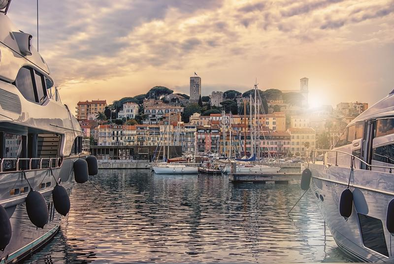 Cannes viewed from the old harbor. City of Cannes at sunset royalty free stock images