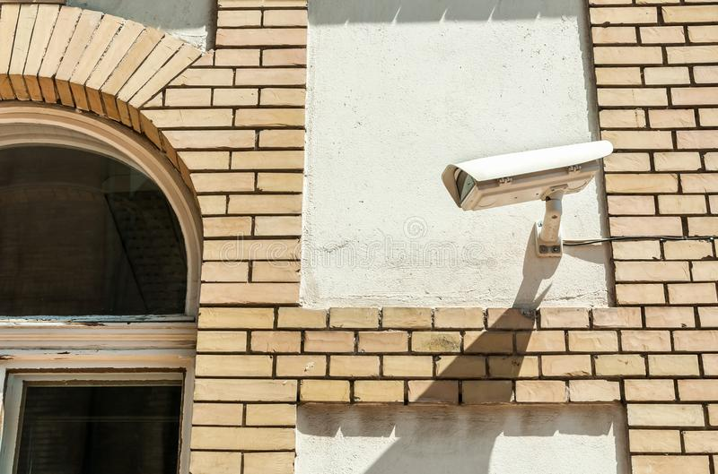 City cctv security surveillance camera system attached on the building brick facade for street public safety.  stock images