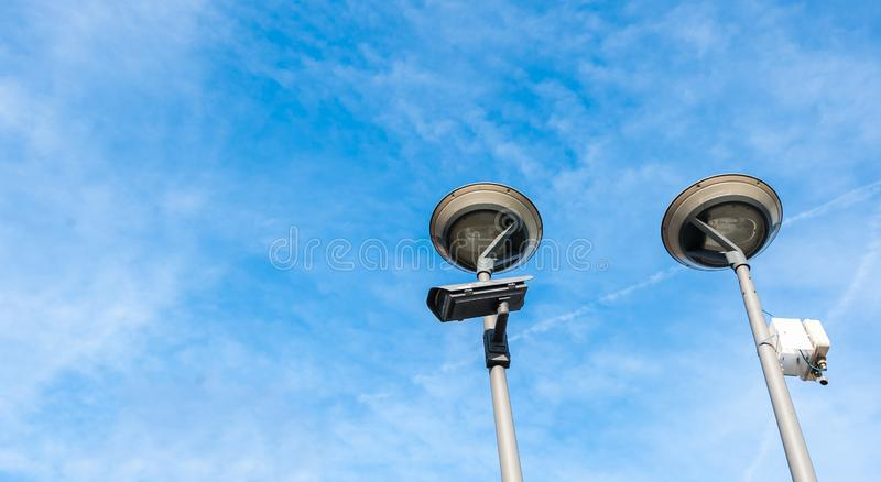 City cctv security surveillance camera system attached on the traffic light pole with clear blue sky background.  stock photography