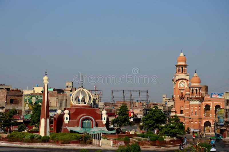 City center with clock tower and contemporary mosque at roundabout Multan Pakistan. Multan, Pakistan - September 16, 2016: The historic clock tower and the main stock photography