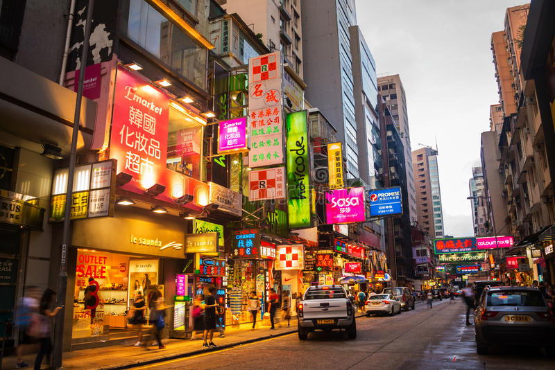 City center in Hong Kong in the evening. HONG KONG - AUGUST 4, 2016: City center with famous street view, parked cars, numerous shops, cafes and restaurants royalty free stock images