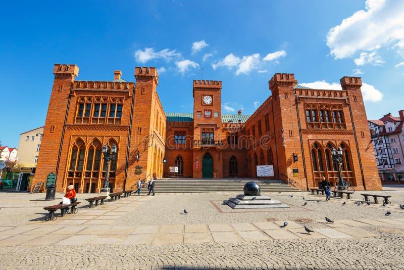 City center of Kolobrzeg with neo gothic building of City Hall, West Pomerania, Poland. Kolobrzeg, Poland - April 08, 2016: City center of Kolobrzeg with neo stock photos