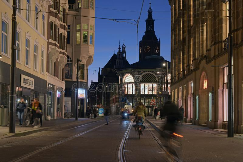 City Lights After Susnet In A City Center With Church With Bikes And People  Walking Around
