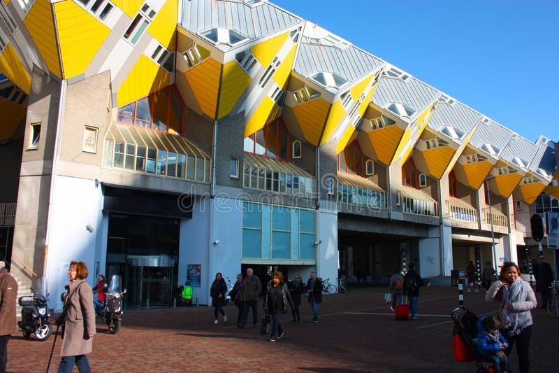 Daily city chaos in the hectic and modern station of the metropolis of Rotterdam. Yellow cubic houses are the decoration of the stock image