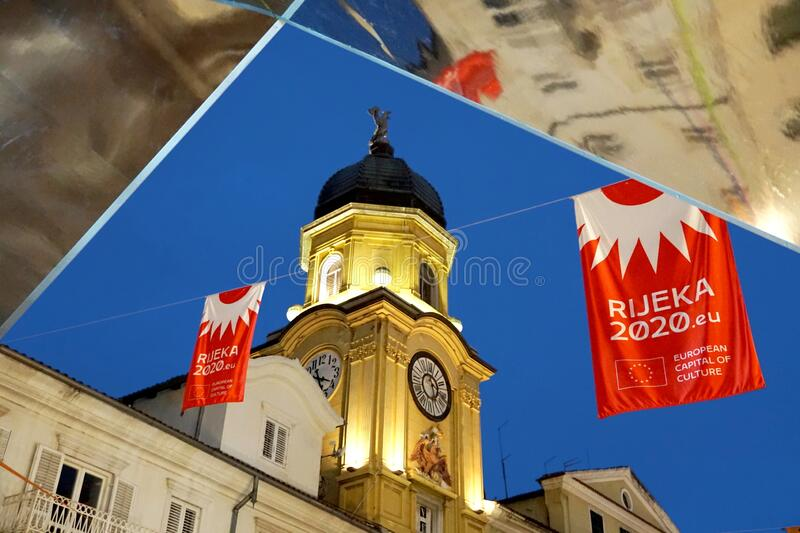 The city clock tower and the flag with the message that the Croatian city of Rijeka is the European Capital of Culture in 2020. View through the part of glass stock photo