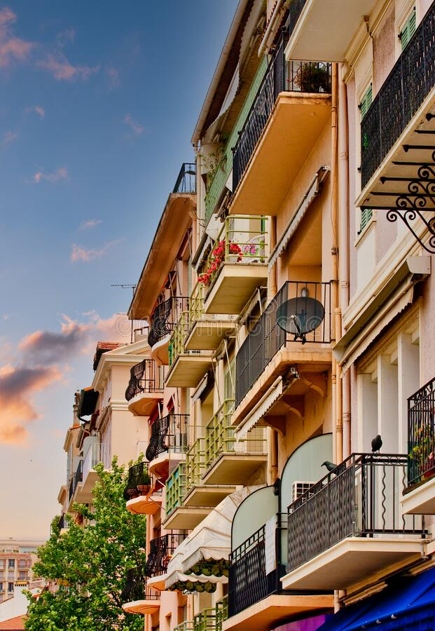 City Condos and Iron Balconies. Pink condos with iron balconies on the streets of Cannes, France stock image
