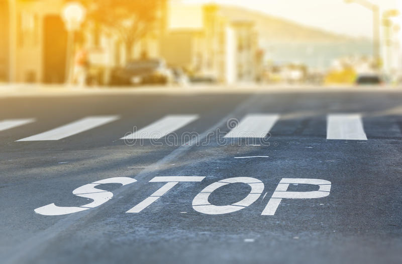 City crosswalk with symbol stop. Closeup road texture with blurred San Francisco Bay in background in a warm sunny day stock photo