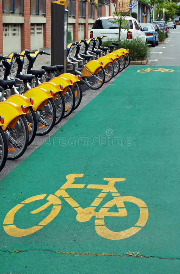 City cycling. Yellow bicycles for hire at a bike station and on-road green cycling path in the city; this active and sustainable public transport option is aimed royalty free stock photos