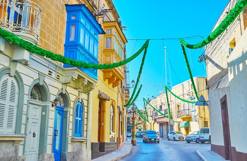 The city decors in Siggiewi, Malta. SIGGIEWI, MALTA - JUNE 16, 2018: The old streets of Siggiewi are richly decorated with green garlands to the feast of St stock photography