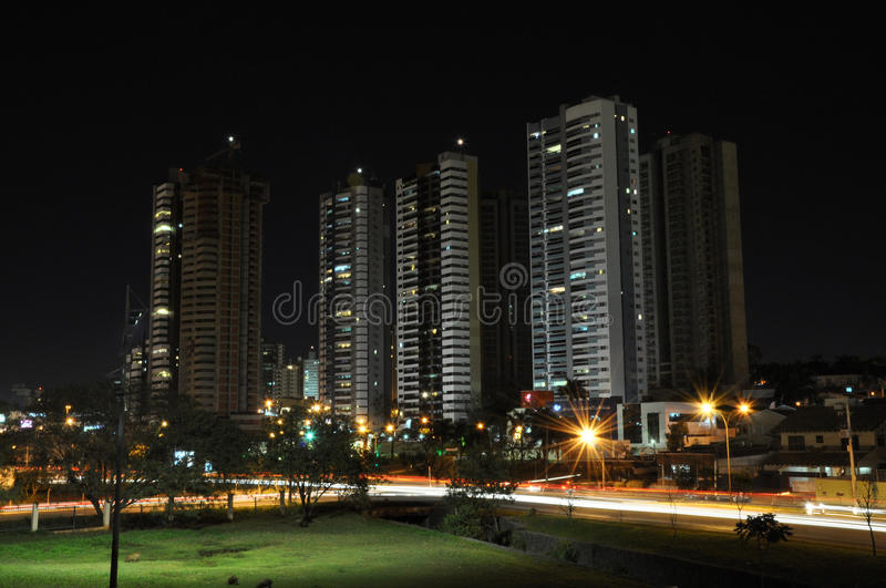 City with few buildings and many lights of cars on the road blurred. stock images