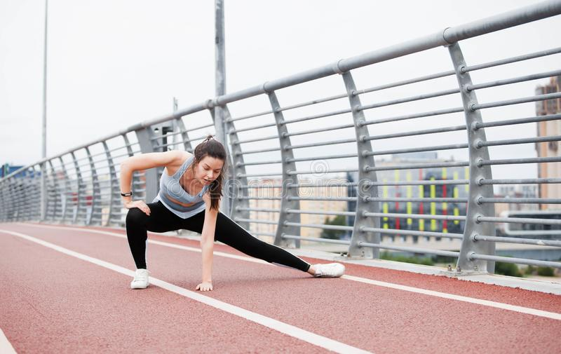 City fitness. A young sports woman in fitness suit is warming up, doing stretching against steel railing of the bridge. stock photos