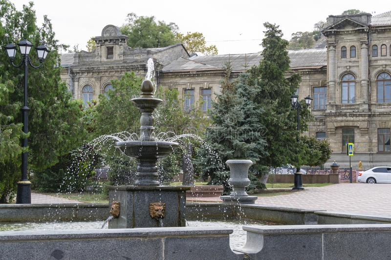 City fountain in heart of historic center in Kerch city on gray building of former women`s gymnasium. City fountain in heart of historic  center in Kerch city on stock photos