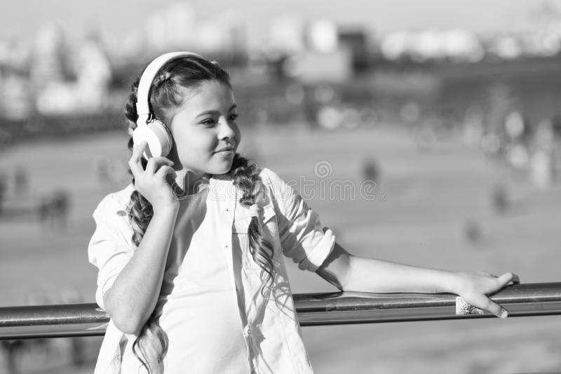 City guide and audio tour. Girl little tourist kid explore city using audio guide application. Free style of travelling stock image