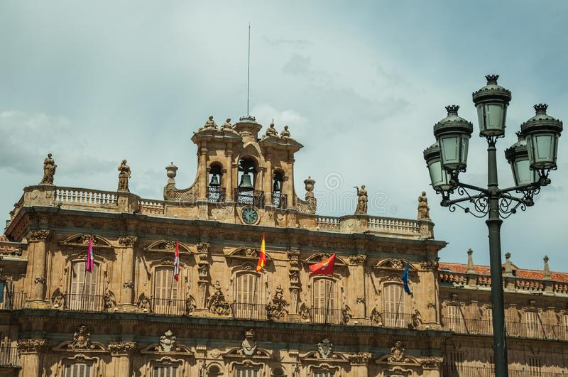 City Hall building with and public lamp at Salamanca. City Hall building facade at the Plaza Mayor, with baroque ornaments and public lamp, in a sunny day at stock photos