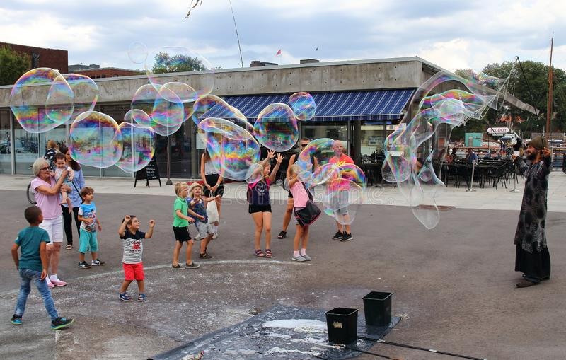 Children playing with local soap bubble artist close to ferry pier to Bygdoy Peninsula in Oslo. royalty free stock photos