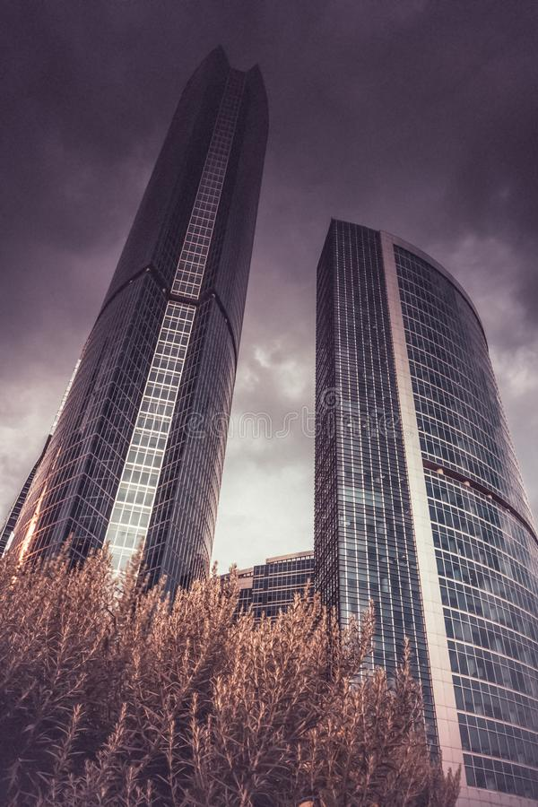 City high rise buildings, cloudy sky background, low angle view. Skyscraper buildings against cloudy sky background. low angle view of office building in royalty free stock photography
