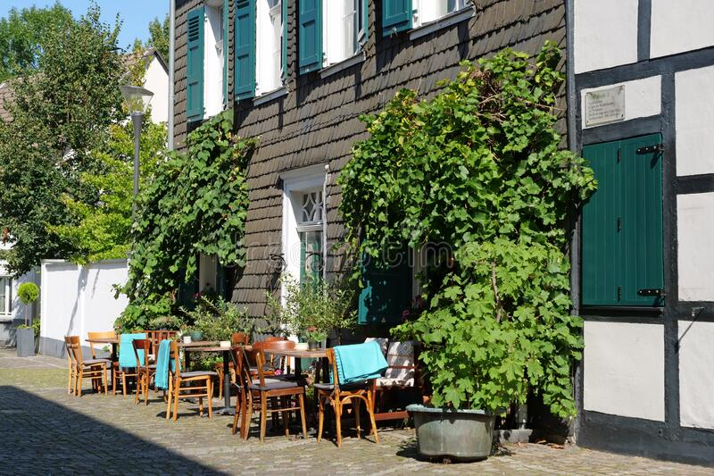 Hilden, Germany, Europe - August 24, 2019: Close-up of the chairs and tables of a little cosy café in a house with slate plates. The city of Hilden belongs to royalty free stock images