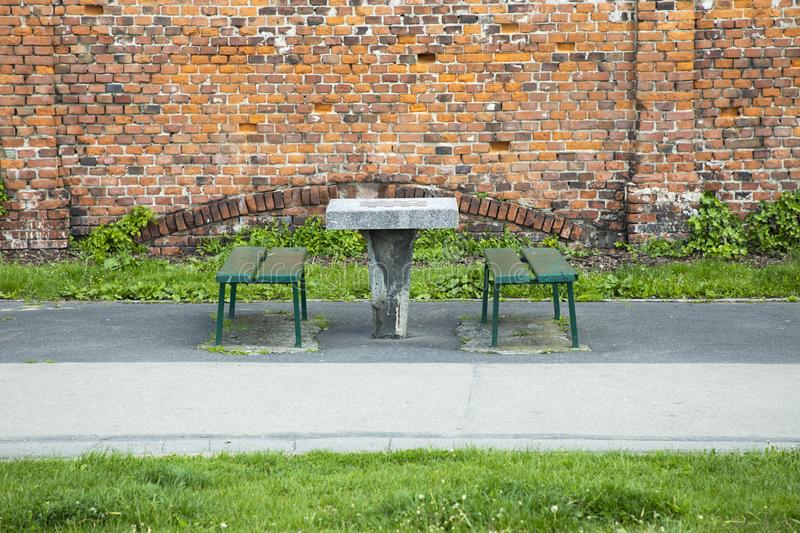 City improvement. Table for playing chess and seats without people outdoors. A chess table and two benches opposite each other in stock photography