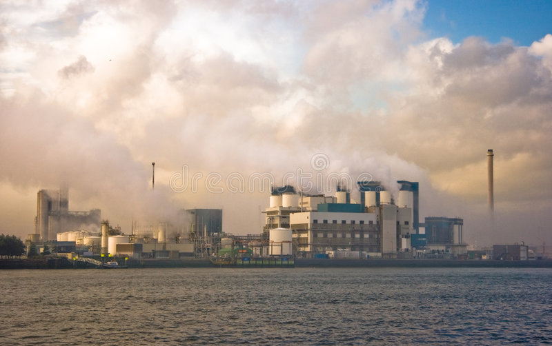 City of industry. Industrial buildings in morning light, clouds and smoke stock photo