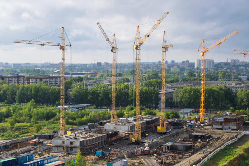 City landscape: construction work. Five cranes in the construction an apartment house, cloudy day in the city stock image