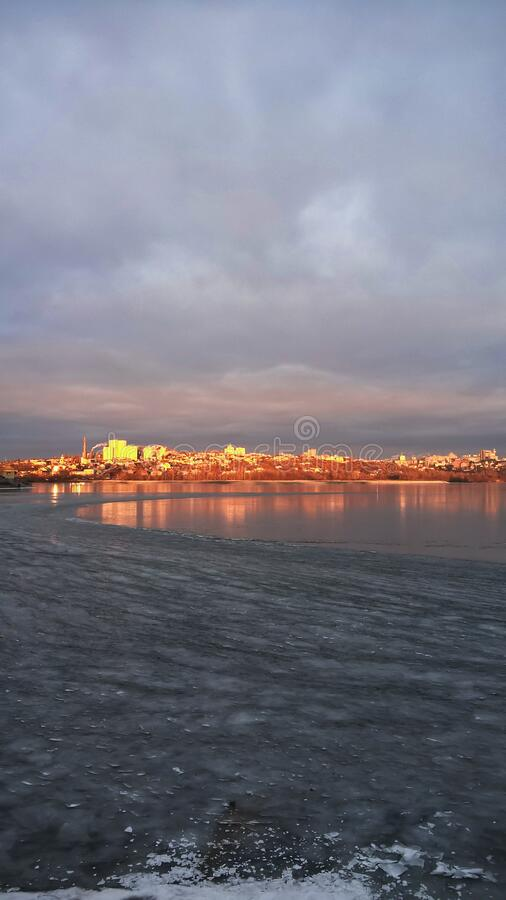 City landscape in winter. City landscape in the light of the dawn sun. Beautiful clouds and houses are reflected in the frozen water on the river. Winter, dawn stock image