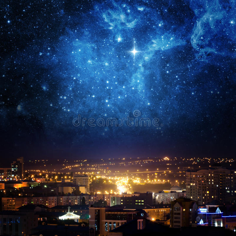 City landscape at nigh with sky filled with stars. Elements of this image furnished by NASA royalty free stock photo