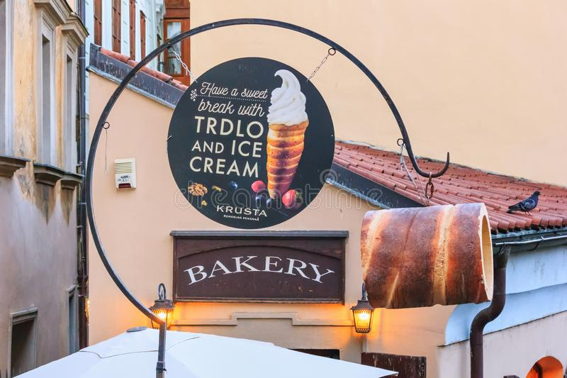 City landscape - view of the signboard of a cafe baking traditional Czech spit cake called Trdelnik or Trdlo royalty free stock images