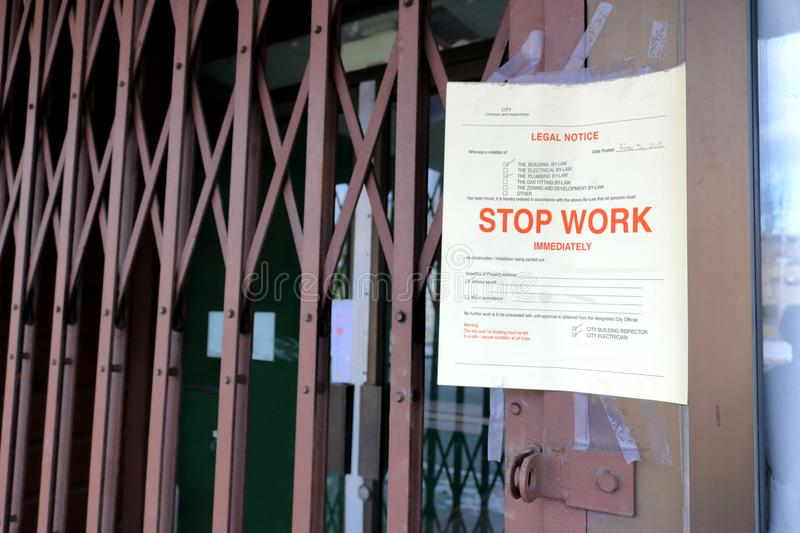 Stop Work City Legal Notice. A city legal notice has been posted on the entrance to a business ordering the owners to stop work on the premises immediately stock photos