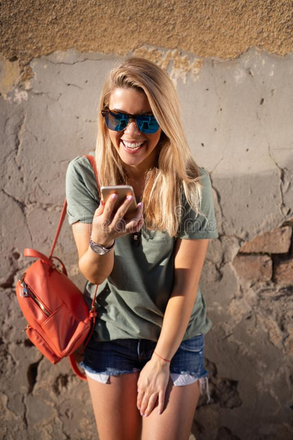 City lifestyle, hipster girl using a phone texting on smartphone app in a street royalty free stock photos