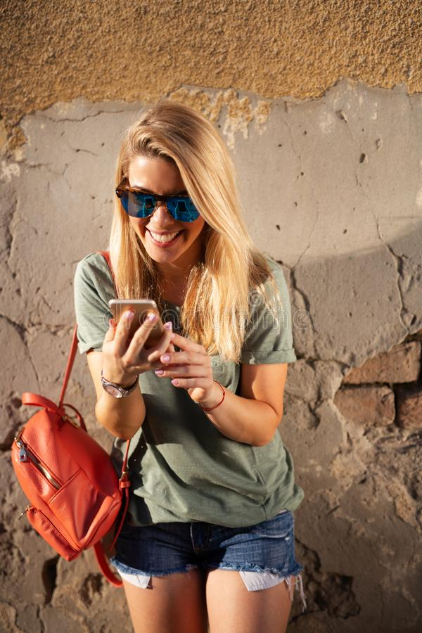 City lifestyle, hipster girl using a phone texting on smartphone app in a street stock images
