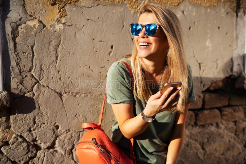 City lifestyle, hipster girl using a phone texting on smartphone app in a street stock photography