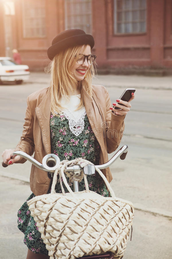 City lifestyle stylish hipster girl with bike using a phone text royalty free stock image