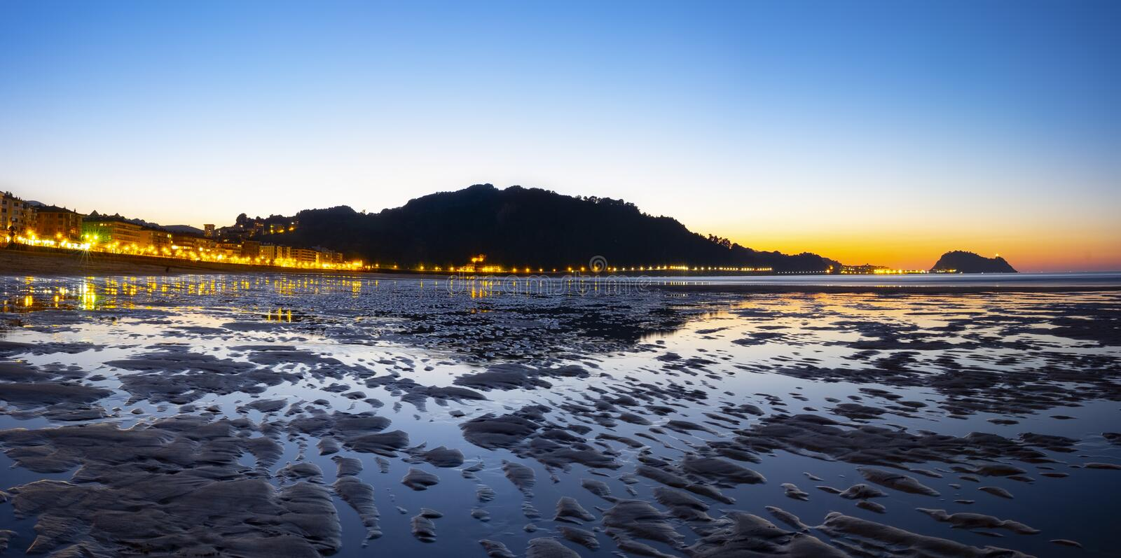 City lights reflected on Zarautz beach at night. Basque Country royalty free stock image