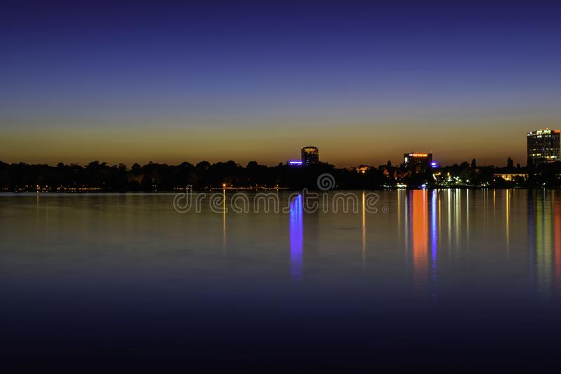 City lights reflecting at night over the water of Herastrau lake stock images