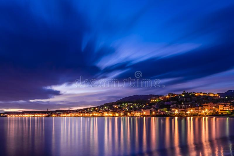 City lights reflecting from sea royalty free stock photography