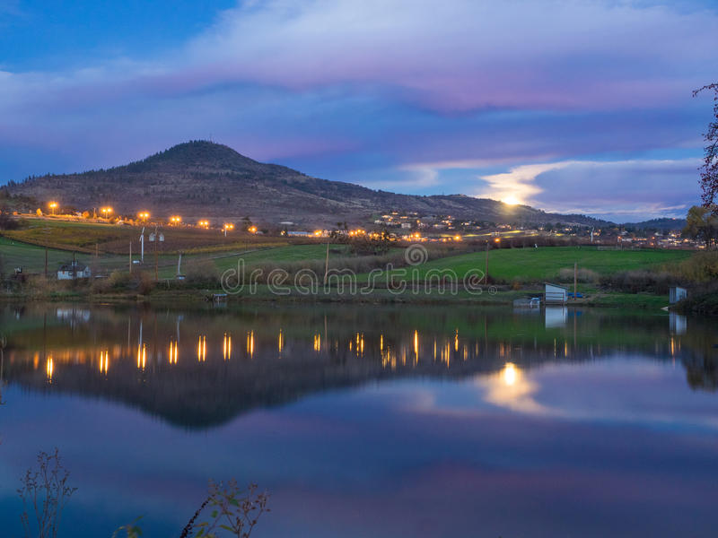 City lights, rising moon and mountain reflected in pond stock images
