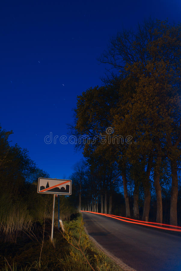 City limits sign at night. Blurred car lights on the night road with city limits sign royalty free stock photography