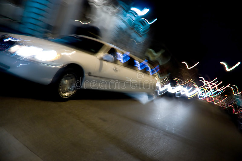 City Limo at Night. An abstract blur of a white limousine in the city at night with light trails stock photography