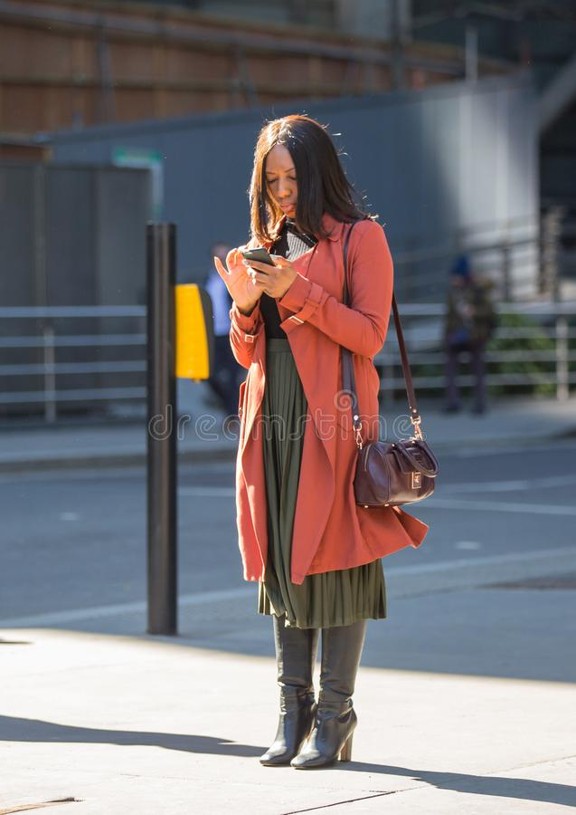 City of London, Woman searching on the phone. UK stock images