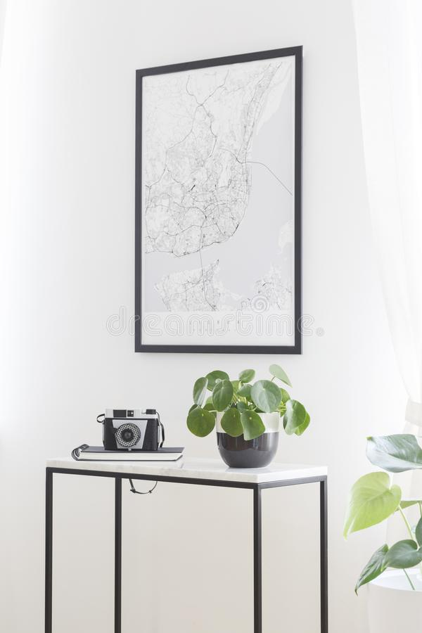 A city map poster on a white wall, plant and camera on a box frame, marble top table in a stylish living room interior for stock photography