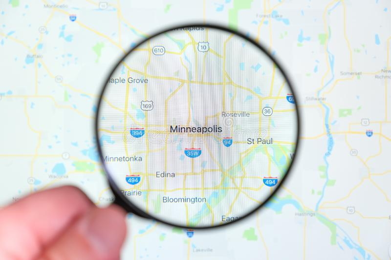 City of Minneapolis, Minnesota on the display screen through a magnifying glass. In a human hand. Selective focus stock photography