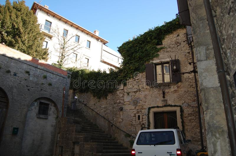 The city on the mountain is San Marino. To save space, the house was built as a continuation of the city wall. Ancient masonry, the house is overgrown with ivy royalty free stock images