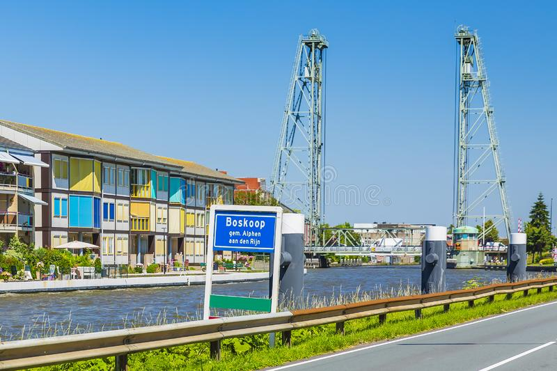 City name sign and vertical lift bridge crossing the river Gouwe at the picturesque village Boskoop, the Netherlands. City name sign in front of contemporary stock photo