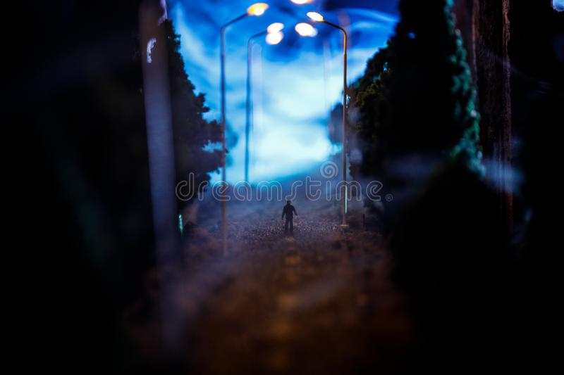 City at night in dense fog. Thick smog on a dark street. Silhouettes of man on road. Table decoration. Selective focus stock photography