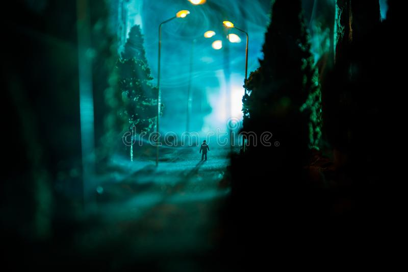 City at night in dense fog. Thick smog on a dark street. Silhouettes of man on road. Table decoration. Selective focus royalty free stock photos